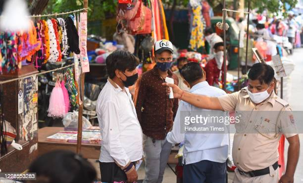 Delhi Police personnel thermal screens a commuter at a weekly market in Pandav Nagar on September 16 2020 in New Delhi India