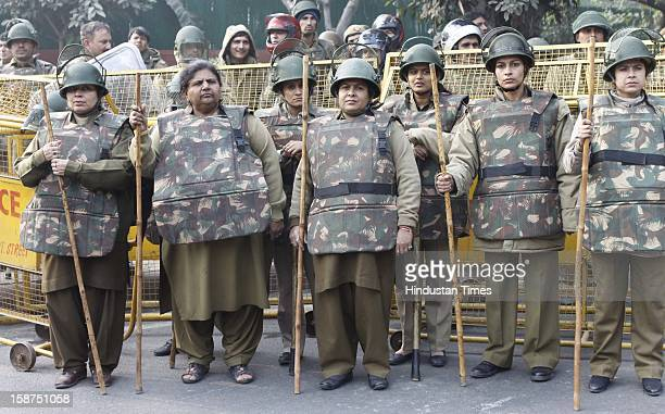 Delhi police stand guard in front of a barricade to stop from approaching a barricade on their way to India Gate while protesting against a recent...