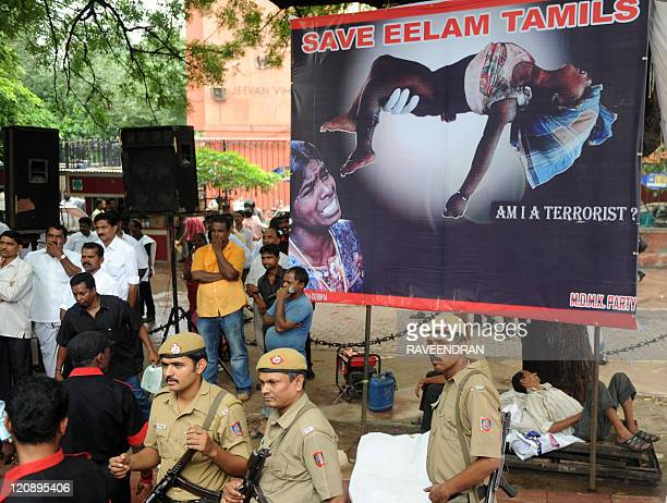 Delhi policemen stand in front a billboard showing Tamil victms from the war during a protest against Sri Lankan President Mahinda Rajapaksa in New...