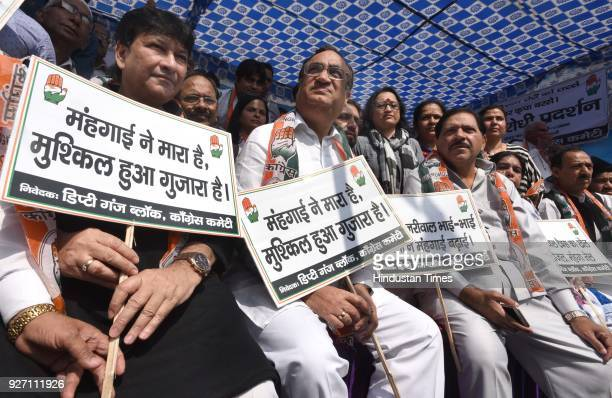 Delhi Pradesh Congress Committee president Ajay Maken with his party workers hold placards during a protest against AAP government for inflation and...