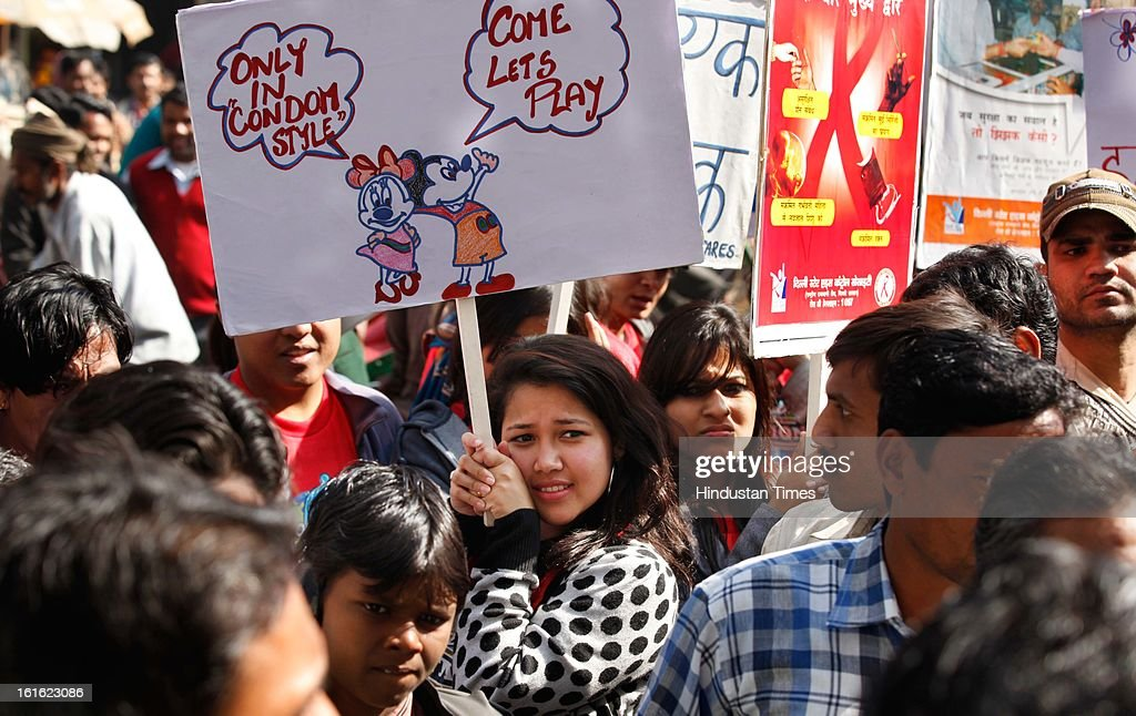 Delhi university students hold placards to spread safe sex awareness on the occasion of International Condom Day on February 13, 2013 in New Delhi, India. AIDS Healthcare Foundation (AHF) organized a 'Safe Sex Awareness' event in the Indian capital to promote the use of condom to prevent spread of HIV infections and sexually transmitted diseases.