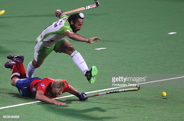 Delhi Waveriders captain Sardara Singh jumps over a Dabang Mumbai player during a match of the Hockey India League on February 5 2015 in Mumbai India