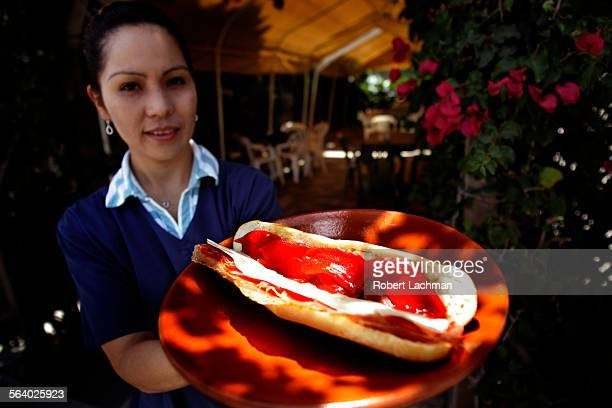 Deli manager Elena Pi–a holds the Bocata de Jamón Serrano sandwich which includes dry–cured Serrano ham imported bread from Spain imported Manchego...