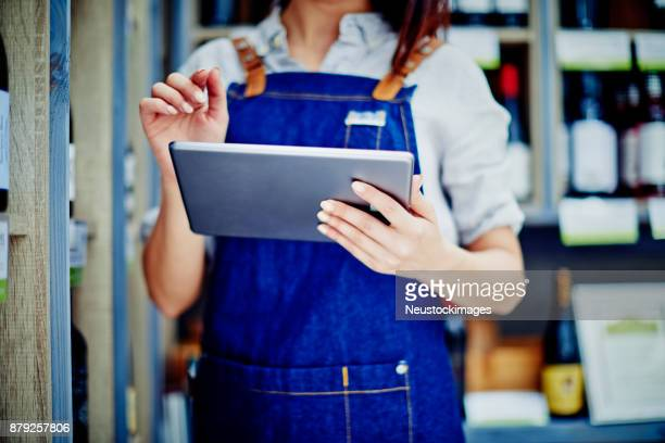 Deli owner holding digital tablet while standing in store