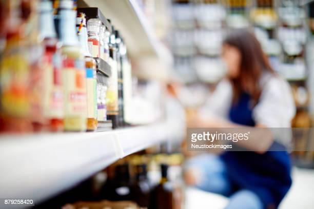 Deli owner kneeling by bottles on shelves in store