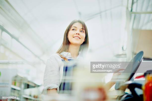 deli owner looking away while using cash register in store - convenience store stock photos and pictures