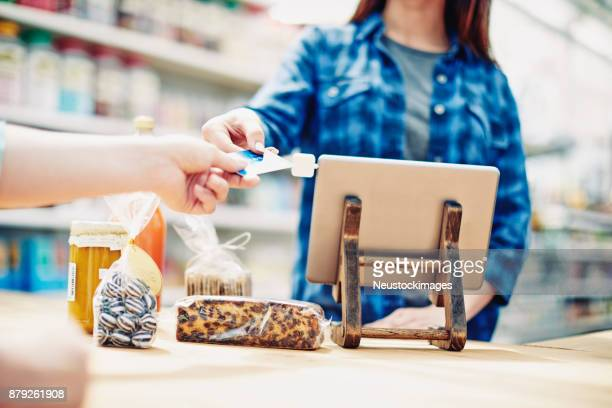 deli owner receiving credit card from customer in store - convenience store counter stock photos and pictures