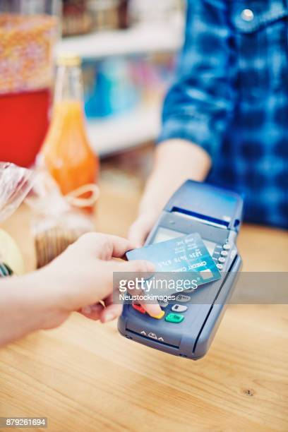 Deli owner receiving credit card payment from customer