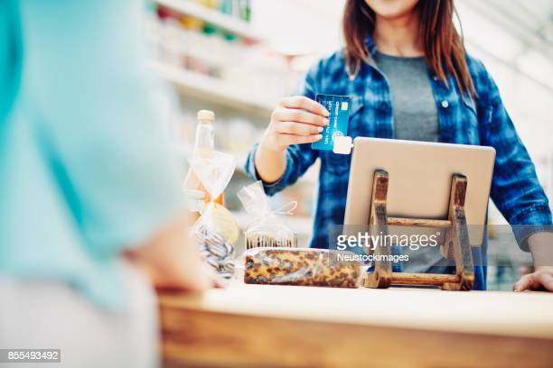 deli owner receiving payment through credit card from customer - convenience store counter stock photos and pictures