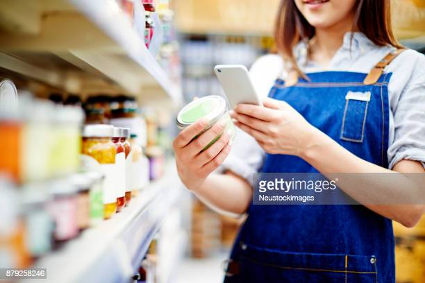 deli owner scanning label on food container with smart phone - mercanzia foto e immagini stock