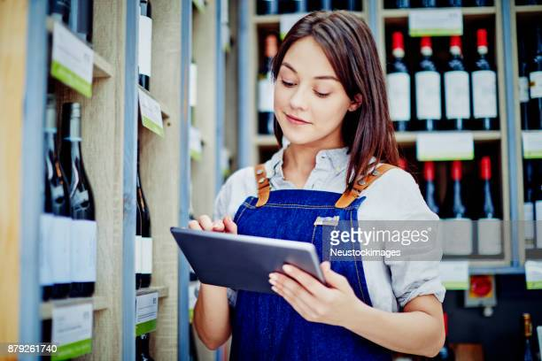 Deli owner using digital tablet at alcohol section in store