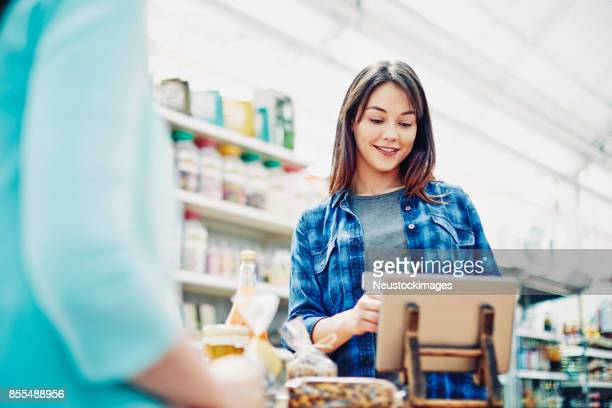 deli owner using digital tablet at checkout counter in store - convenience store counter stock photos and pictures