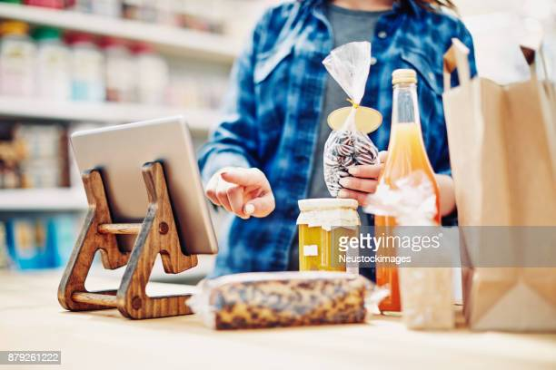 Deli owner using digital tablet while holding food package