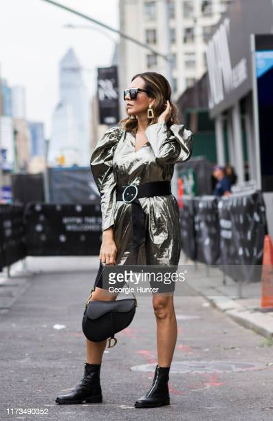 Delia Hickman wearing silver metallic puff shoulder sleeve top, oversized gold earrings, black suede waist belt, black biker shorts, black leather...