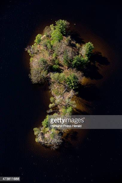 A deliberate underexposure turns the water to black and isolates this small island on Lake Auburn as seen in this aerial photograph taken Thursday...