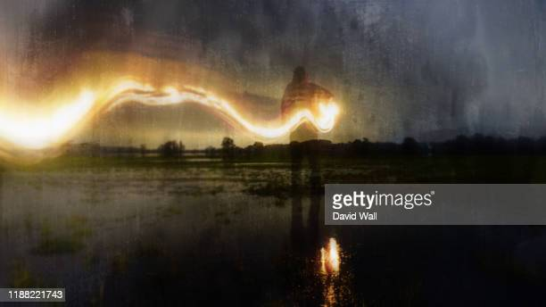 a deliberately blurred, abstract, out of focus, textured edit. of a ghostly, eerie figure, standing in a flooded field, holding a glowing lamp with a flaming light trail behind. on a winters evening. - paranormal stock pictures, royalty-free photos & images