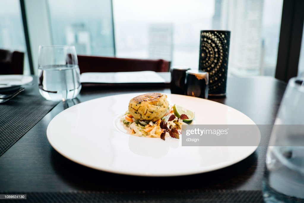 Delicate appetizer of crispy crab cake with fresh green salad served on table in a restaurant : Stock Photo
