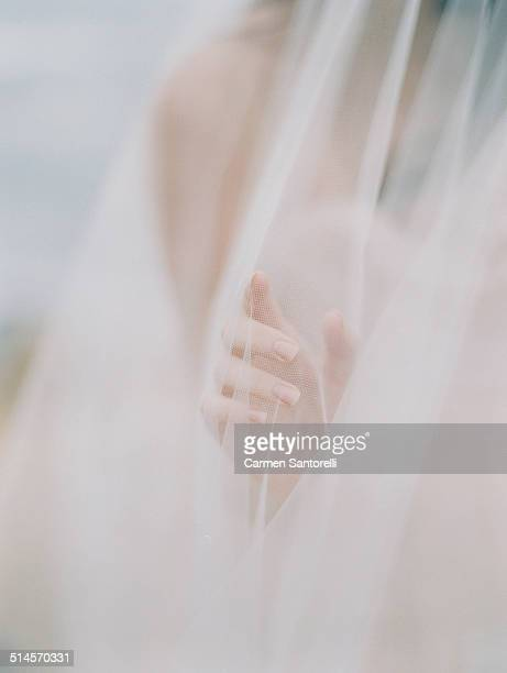 delicate bride hand reaching through veil - ベール ストックフォトと画像