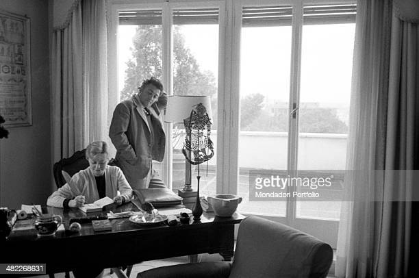 A delicate domestic scene in the sunny house of Federico Fellini and Giulietta Masina the movie director leaning on the french windows overlooking...