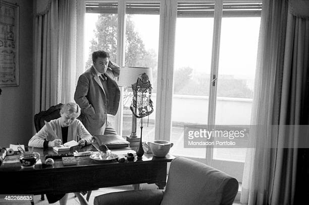 A delicate domestic scene in the sunny house of Federico Fellini and Giulietta Masina the movie director standing by the french window overlooking...