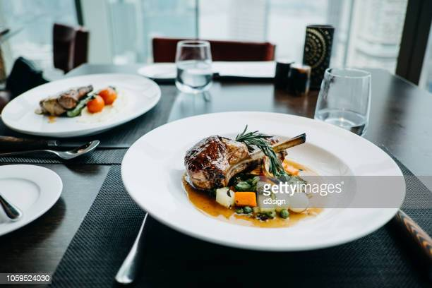 delicate main course of braised lamb chop and steak freshly served on table in a restaurant - fine dining stock pictures, royalty-free photos & images