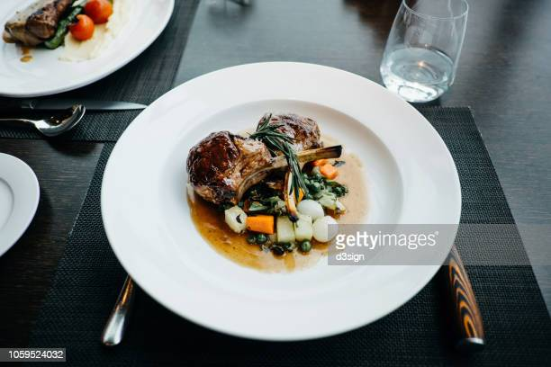 delicate main course of braised lamb chop with a mix of vegetables freshly served on table in restaurant - gravy stock photos and pictures