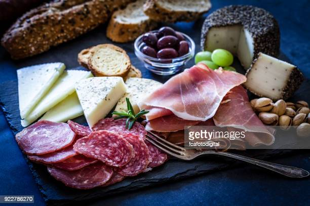 delicious appetizer on bluish tint table - delicatessen stock pictures, royalty-free photos & images