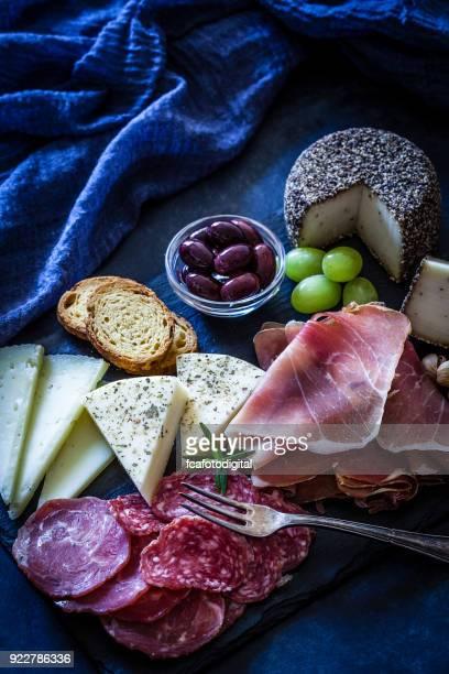 Delicioso aperitivo en mesa de tinte azulado