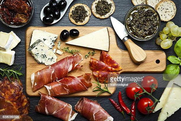 delicious appetizer on dark slate table - delicatessen stock pictures, royalty-free photos & images