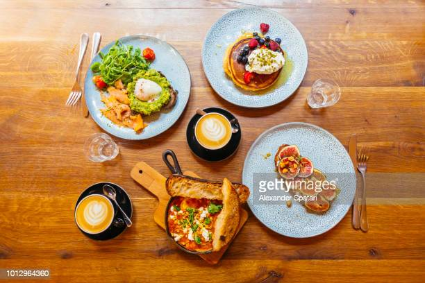Delicious brunch with smashed avocado on toast, salmon, pancakes with fresh berries, fig toast and shakshuka, directly above view on wooden table