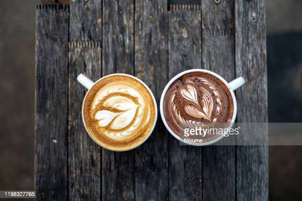 delicious flat white coffee and hot chocolate with froth art on top of wooden table - mocha stock pictures, royalty-free photos & images
