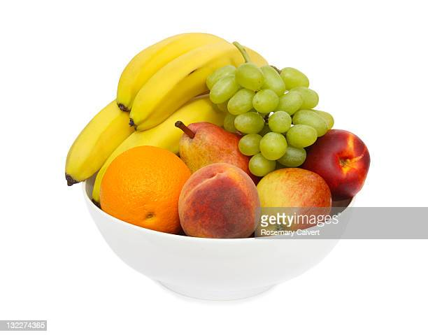 Delicious fresh fruit piled high in a white bowl.