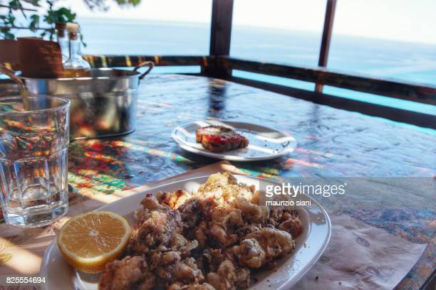 Delicious fried calamari on wooden table with glasses and plates