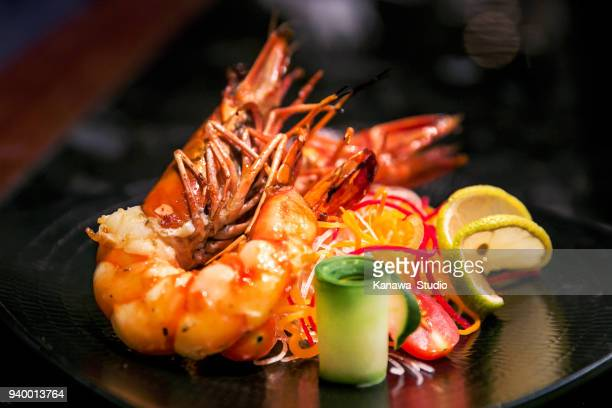 delicious grilled king prawns with lemon - tapas stock photos and pictures