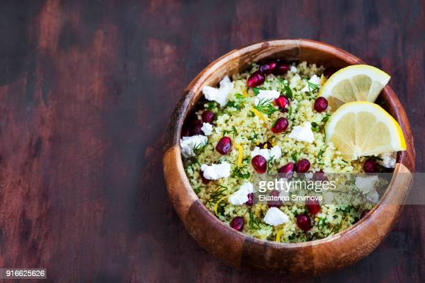 delicious healthy cous cous salad with herbs, lemon zest, feta cheese and pomegranate seeds - moroccan culture stock photos and pictures
