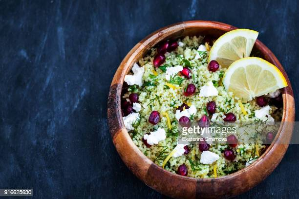 delicious healthy cous cous salad with herbs, lemon zest, feta cheese and pomegranate seeds - moroccan culture stock pictures, royalty-free photos & images