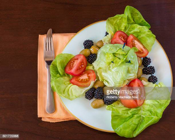 Delicious healthy garden salad with Boston lettuce tomatoesgreen olives stuffed with garlic and blackberries for a contrast in flavor