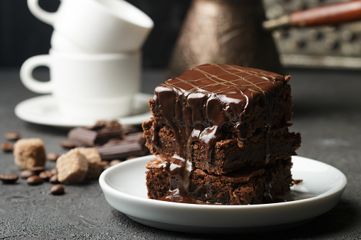 Delicious homemade brownie with chocolate sauce and caramel on the table. Selective focus 689260420