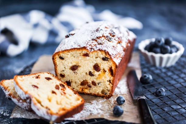 Delicious homemade cottage cheese and raisins loaf cake on blue background, close up