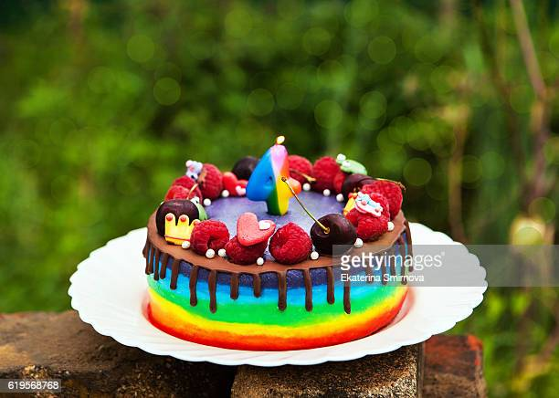 Delicious homemade rainbow cake for kid decorated with fresh berries