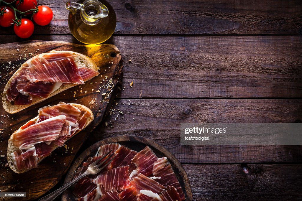 Delicious Iberico ham tray shot on rustic wooden table : Stock Photo