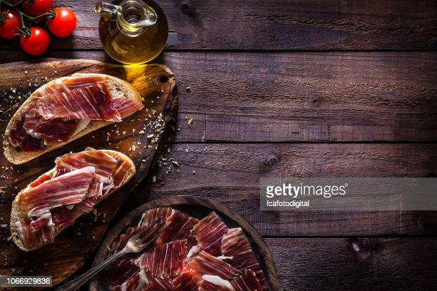 delicious iberico ham tray shot on rustic wooden table - ham stock pictures, royalty-free photos & images