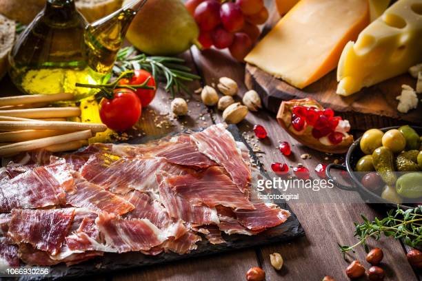 delicious iberico ham tray shot on rustic wooden table - serrano ham stock photos and pictures