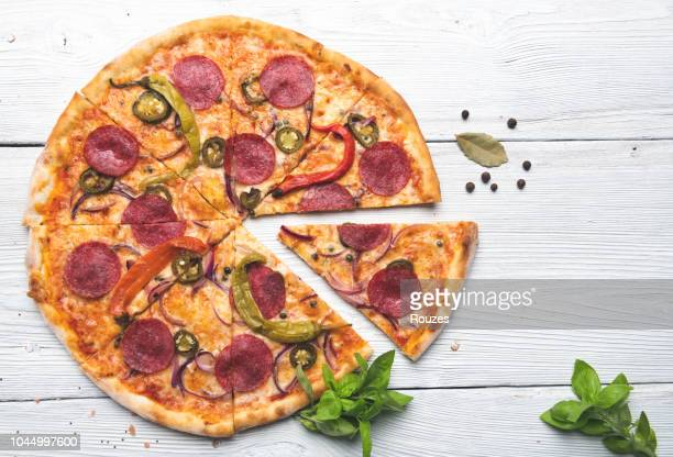 delicious pizza isolated on white wooden background - pepperoni pizza stock photos and pictures