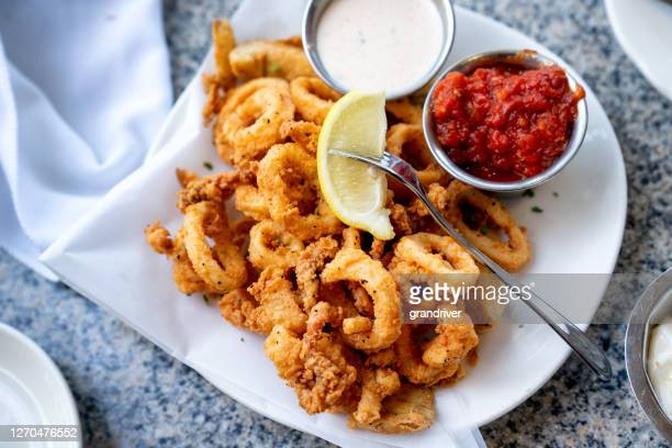 a delicious plate of deep fried calamari, squid fried to perfection cajun style, served with a side of freshly made garlic aioli sauce and cocktail sauce, fresh lemon wedges on the side - fried stock pictures, royalty-free photos & images