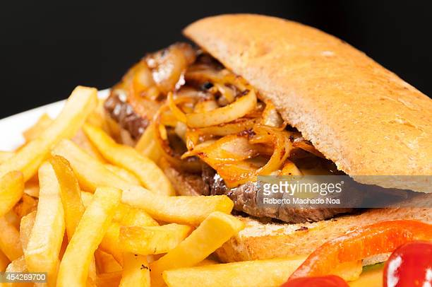 Delicious Pork Steak Sandwich in soft bun served with lot of caramelized onions and french fries also garnished with cherry tomatoes and peppers