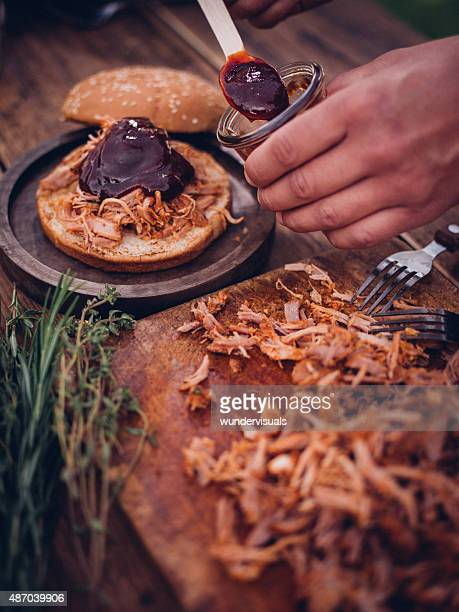 Delicious pulled pork and sauce going into a burger
