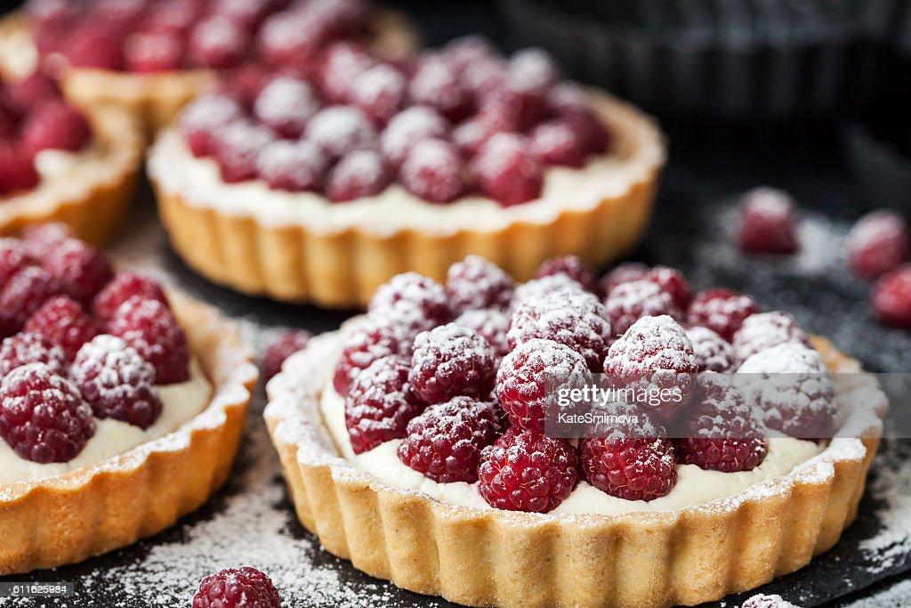 Delicious raspberry mini tarts on dark background : Stock Photo