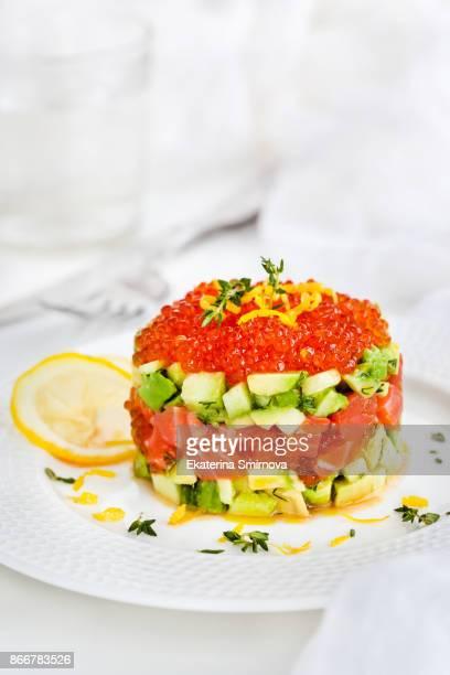Delicious red caviar, salmon, avocado and cucumber tartar