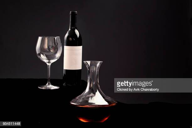 delicious red wine bottle and glass filled with wine on black background - cabernet sauvignon grape stock pictures, royalty-free photos & images
